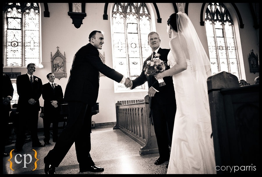 groom shaking hands with bride's father at the end of the aisle