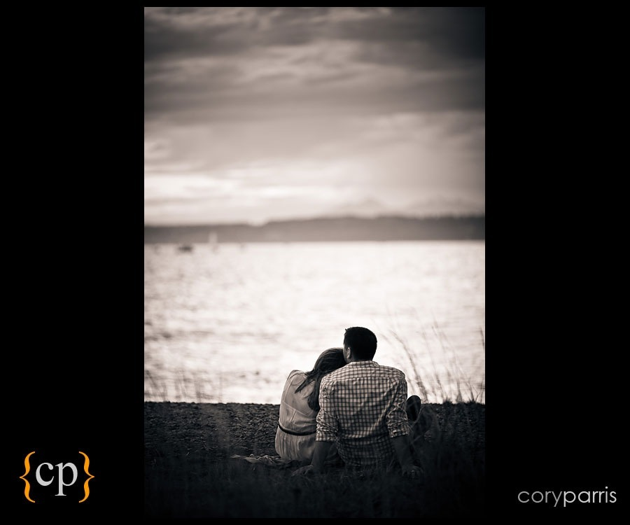 couple sitting on the beach looking at the mountains by seattle wedding and portrait photographer cory parris