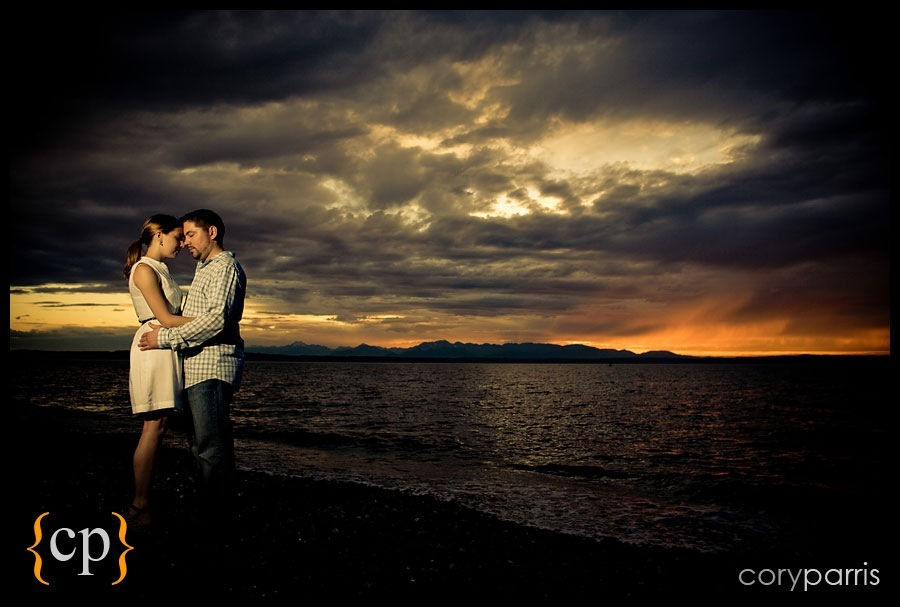engagement portrait on the beach at golden gardens with dark, moody clouds