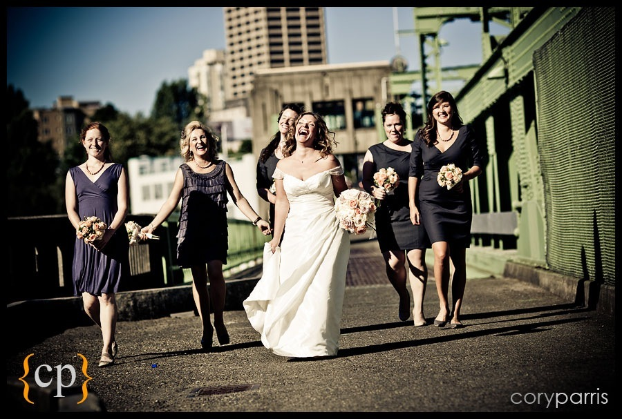 bride and bridesmaids laughing on a bridge in seattle
