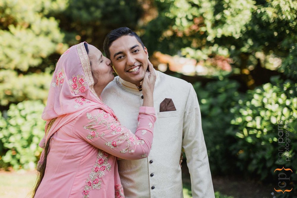 Alam's mom gives him a kiss after the ceremony.