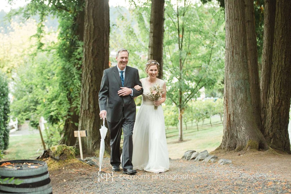 Bride walking with her dad through the trees
