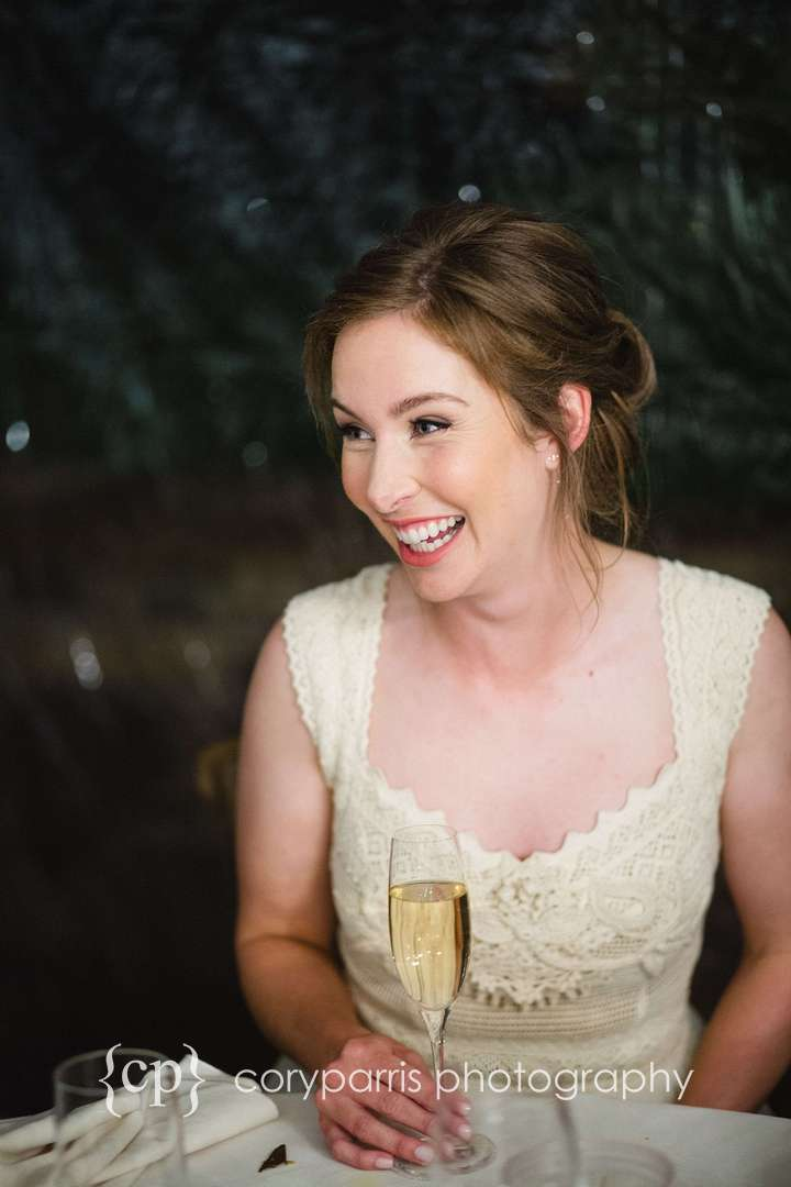 Bride laughing at toasts during her DeLille Cellars wedding reception