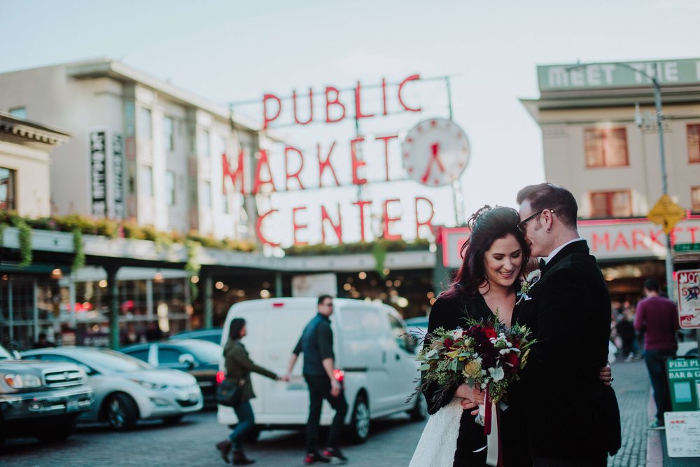 Katie and Brian at their first look on their wedding day on the streets of Seattle in front of Pike Place Market