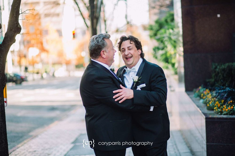 The two grooms laughing together during portraits on the streets of Seattle
