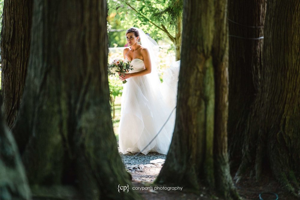 Ashley making her way through the trees to her wedding