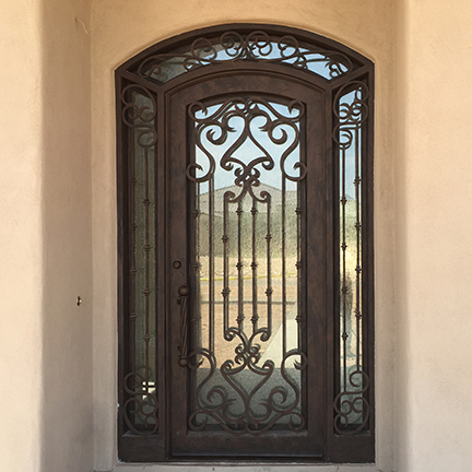 Arched ornamental wrought iron door wit side light.jpg