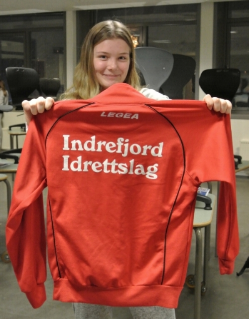 A student showing off her handball team sweatshirt.