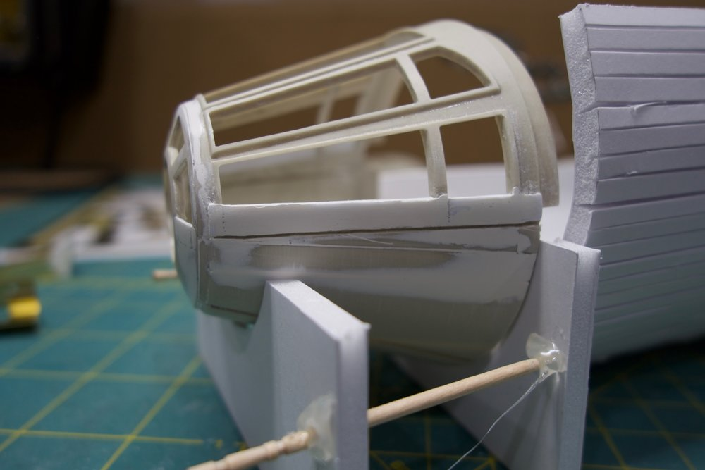 I used a bit of epoxy to start filling in the gaps and old panel lines, while slightly reinforcing the stacked styrene.