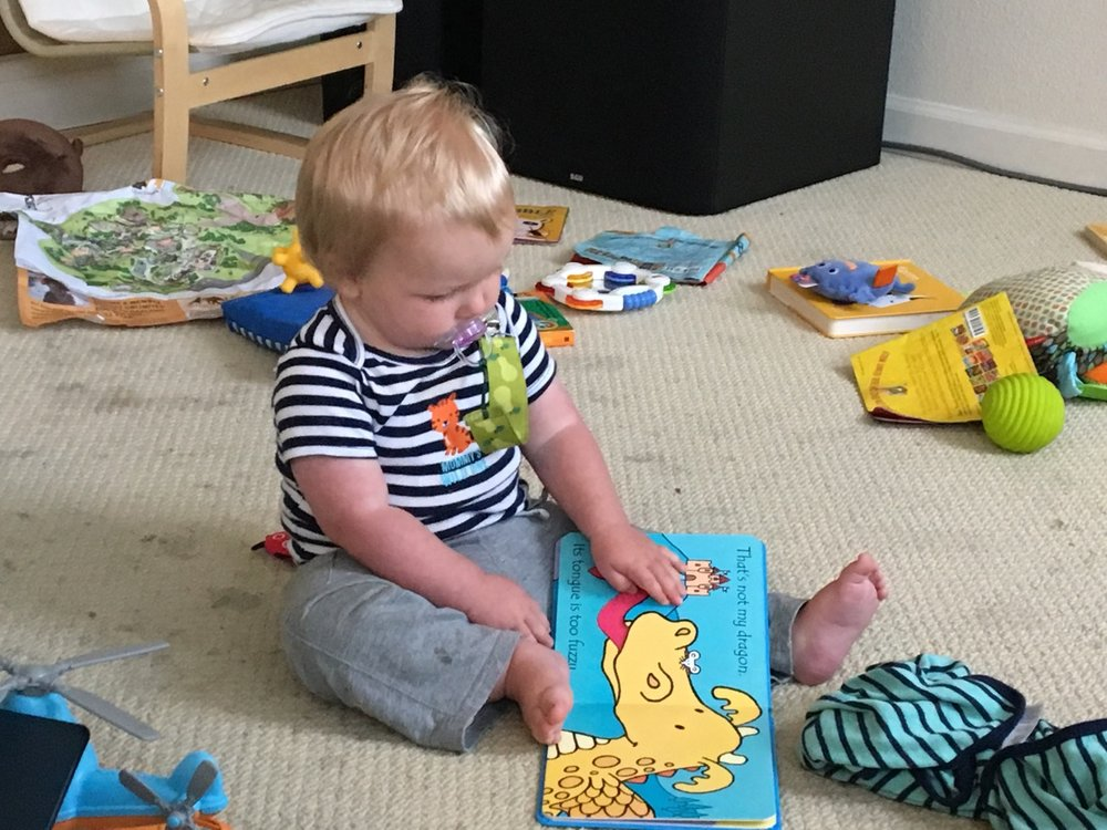"""Reading"" his That's Not My Dragon book"