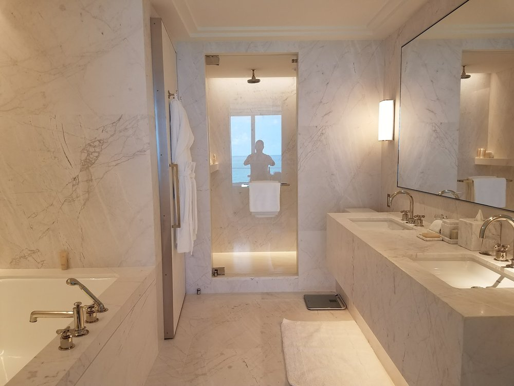The huge bathroom with tub and separate rain shower, all carved out of marble.
