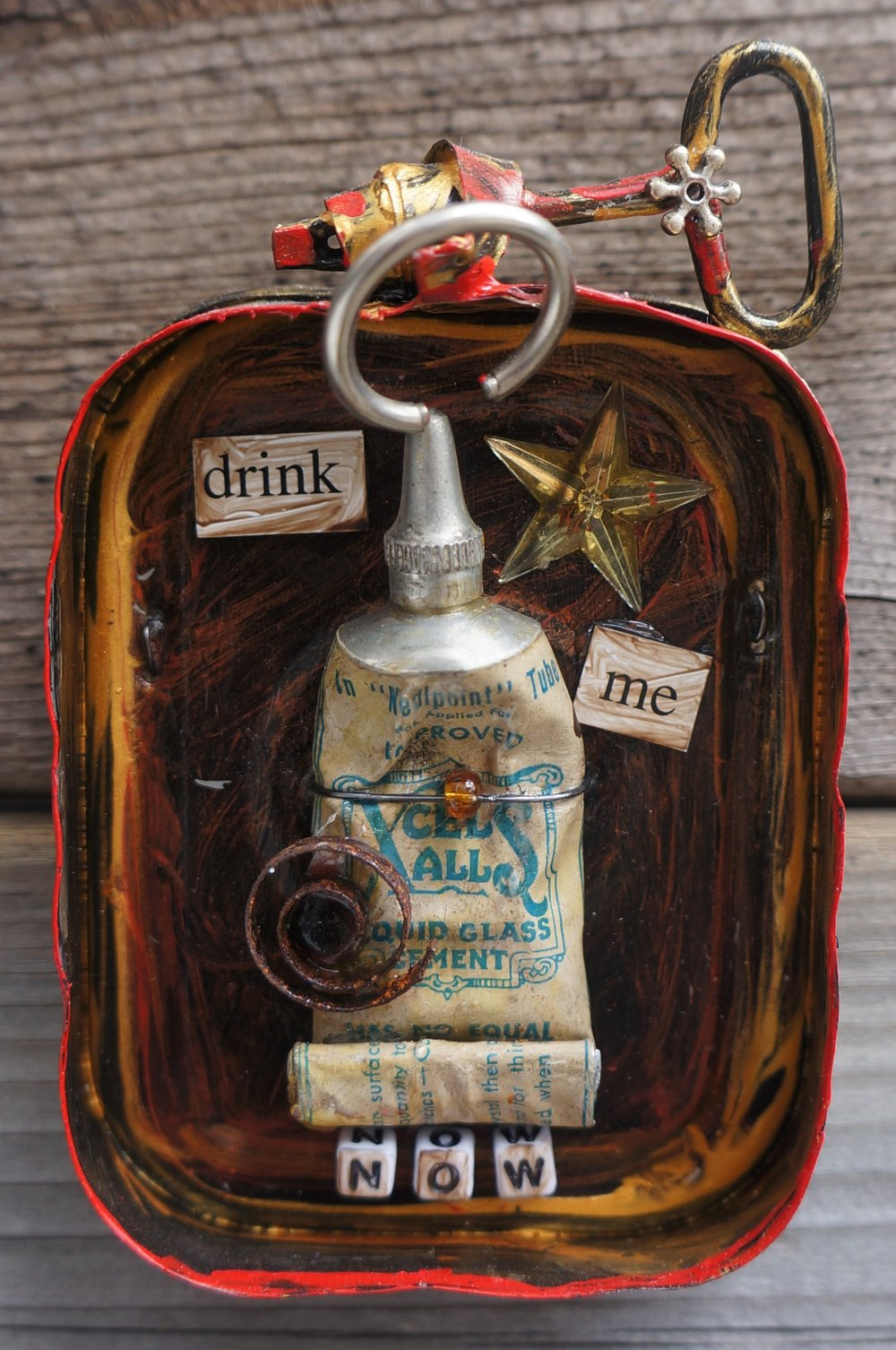 Mixed media collage in the lid of a corned beef tin. Found objects, paint, magnetic text.