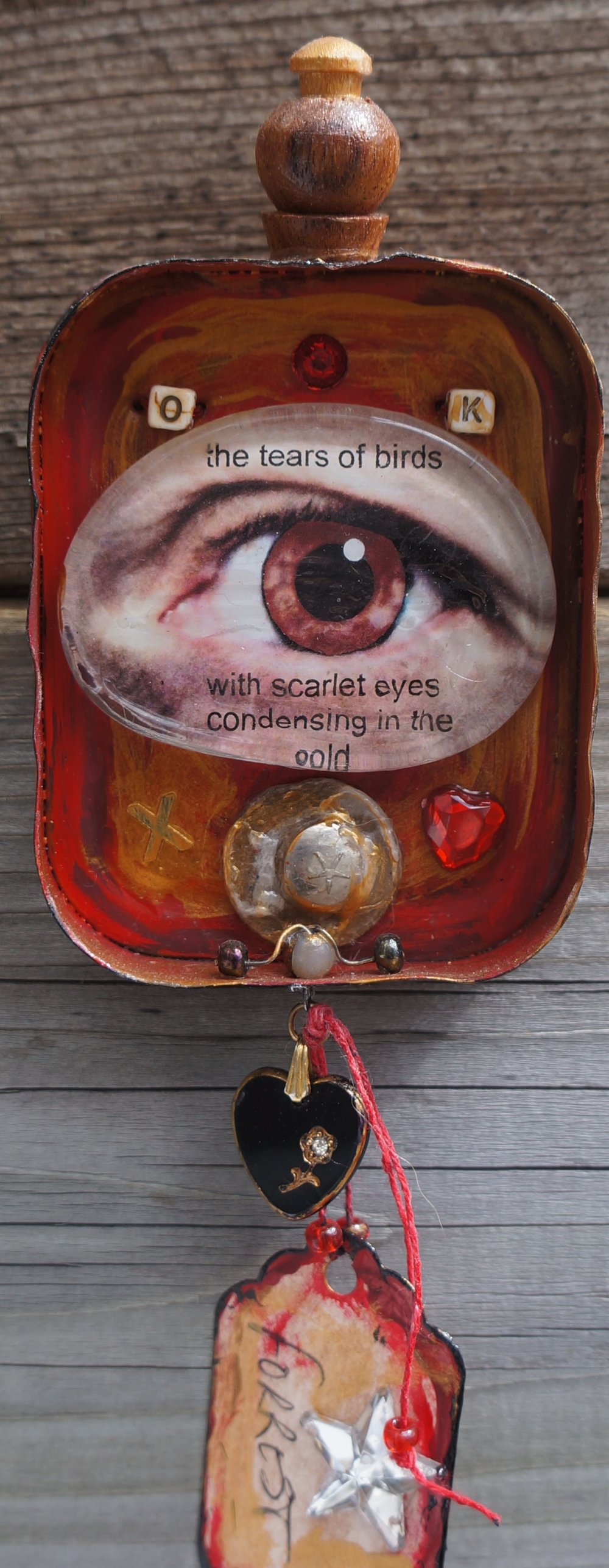 Mixed media collage in the lid of a corned beef tin.  Found objects, glass glob with photograph of my eye, tag, beads, paint.