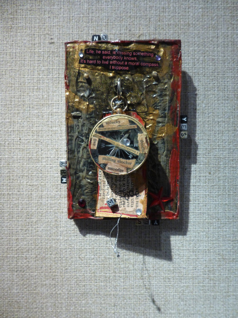 """the oracle of pain"", mixed-media collage.  Wood, acrylic paint, found objects, beads, tag, compass, text:  ""Life; he said, is missing something,  everybody knows,  it's hard to live without a moral compass,  I suppose""."
