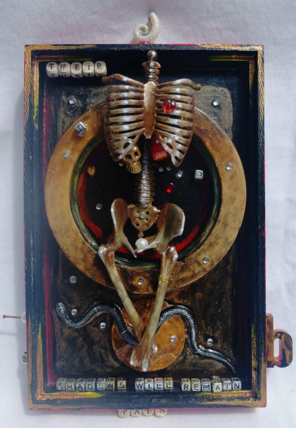 """the house of pain"", mixed-media collage.  Shadow box, dollar store skeleton, plastic snake, shell from New Zealand, beads, text."