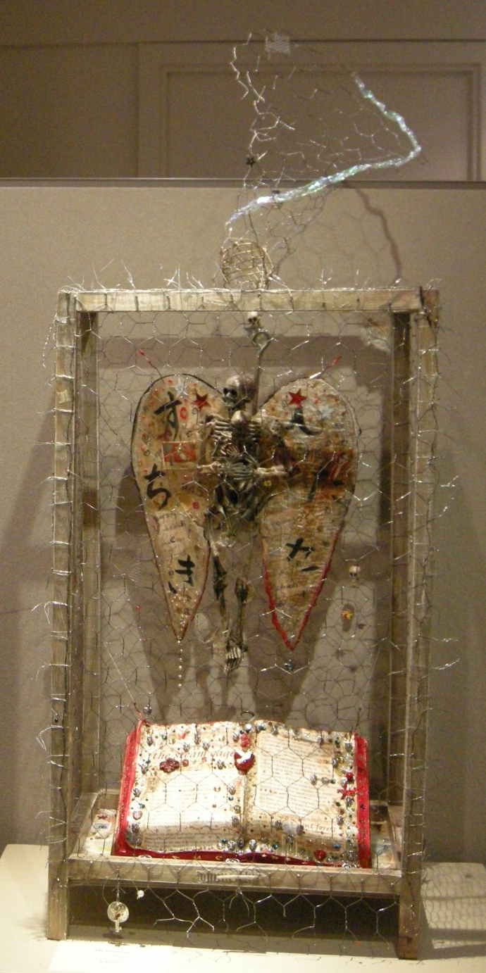 """the steam cage"" - mixed-media collage, chicken wire, wood, plastic skeletons, found fiberglass wing, beads, book,  shark hook, text.  Lindsay Gallery 2011."