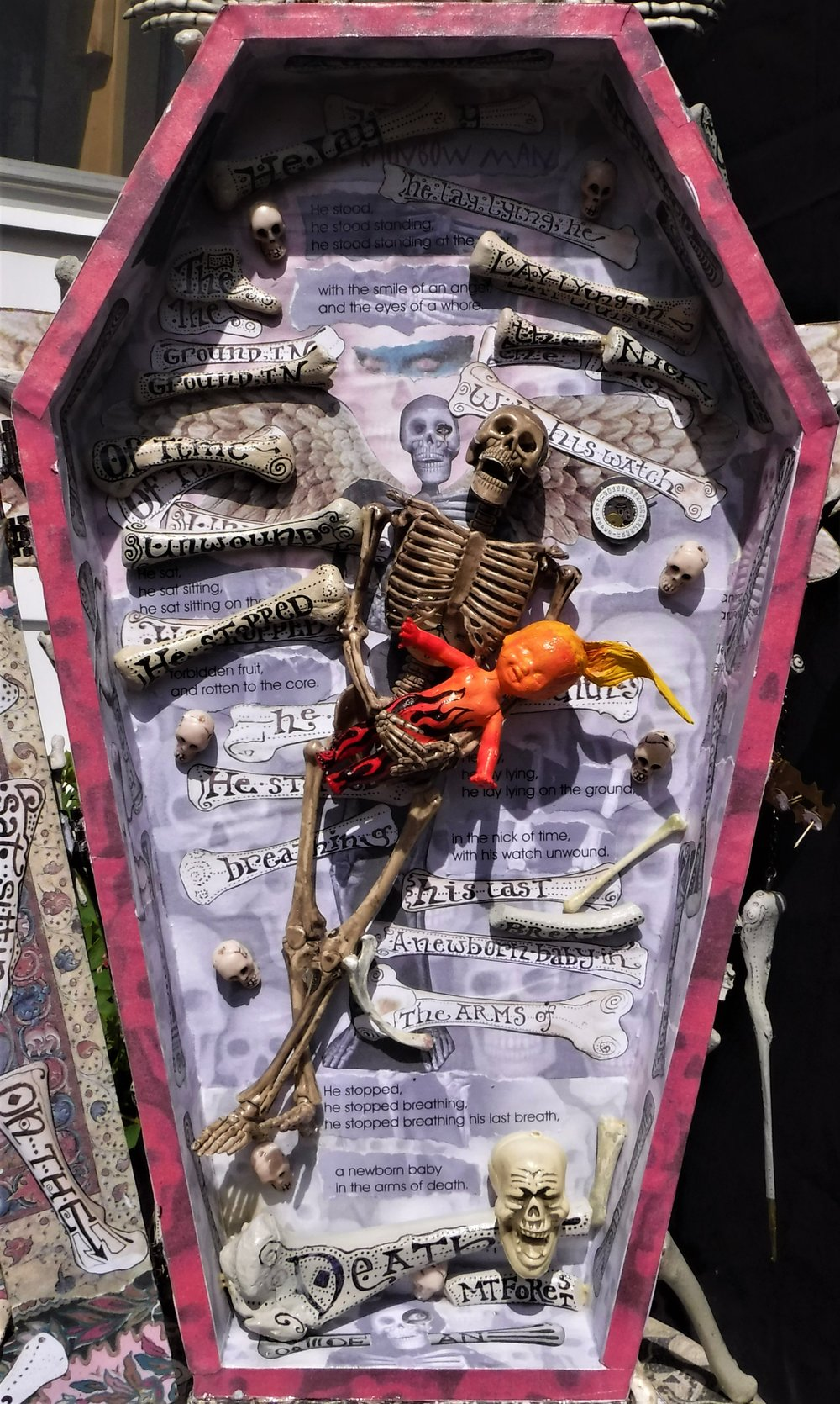 """the rainbow man"" - interior, plastic dollar store skeleton, doll, acrylic paint, chicken bones, text."