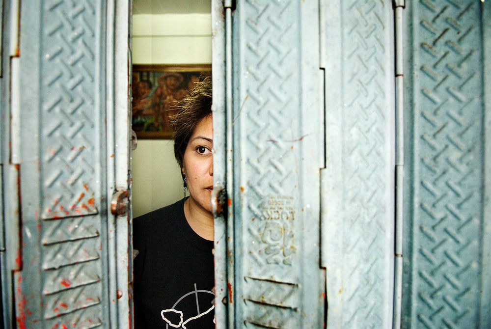 Human Rights lawyer Beverley Longid hiding behind the blinds of a window (©2009 Bart De Bock)