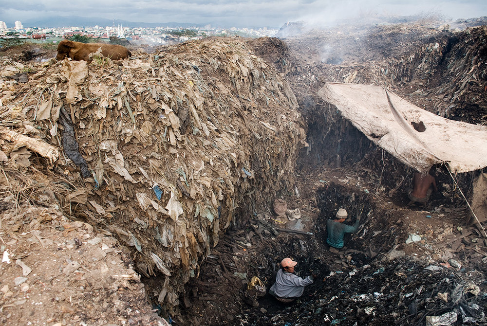 Scavengers of Smokey Mountain dig the landfill for iron, metal scraps and other materials buried under the waste.