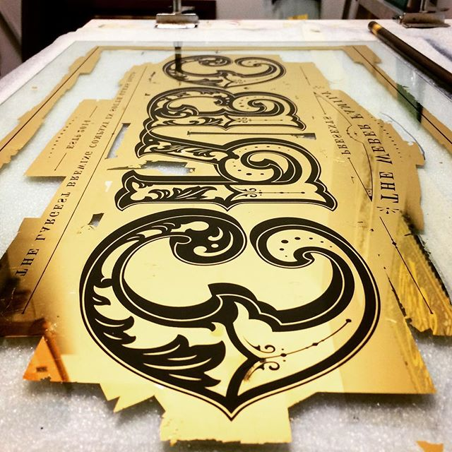 Process image of the the glass sign Im currently working on. Two layers of 23k gold with small bursts of 12k silver leaf inside of the design. Design is now screen printed on and this will soon come properly to life. one more stage of gold leaf gilding, then a few coats of paint left, then were home🙌🏻 #reverseglass #design #lettering #glasssign #23k #gold #goldleaf #victorian #craftsmanship #craft #type #typography #allcaps #ornament #illustration #graphicdesign #paint #ink #screenprinting #screenprint