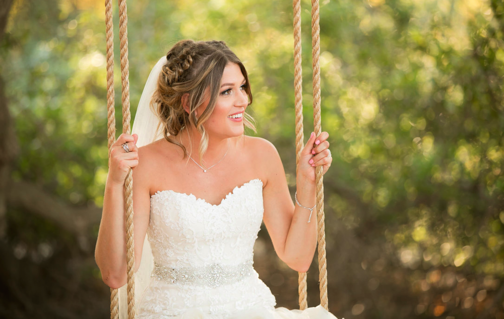 Wedding Hairstyle with Braided updo, Veil and Natural Makeup. Photos taken outside on Swing. Bridal hair and makeup by Vanity Belle in Orange County (Costa Mesa) and San Diego (La Jolla)