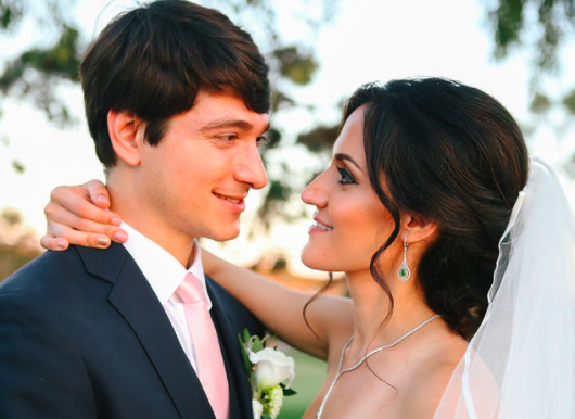 Brunette Bride with Updo Hairstyle and Veil Looking into Husband's Eyes in Outdoor Wedding Photos. Bridal hair and makeup by Vanity Belle in Orange County (Costa Mesa) and San Diego (La Jolla)