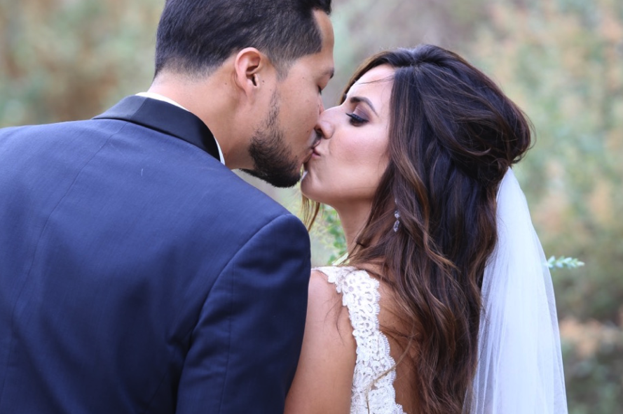 Brunette Bride with Veil and Hair down Kissing Husband in outdoor wedding photos. Bridal hair and makeup by Vanity Belle in Orange County (Costa Mesa) and San Diego (La Jolla)