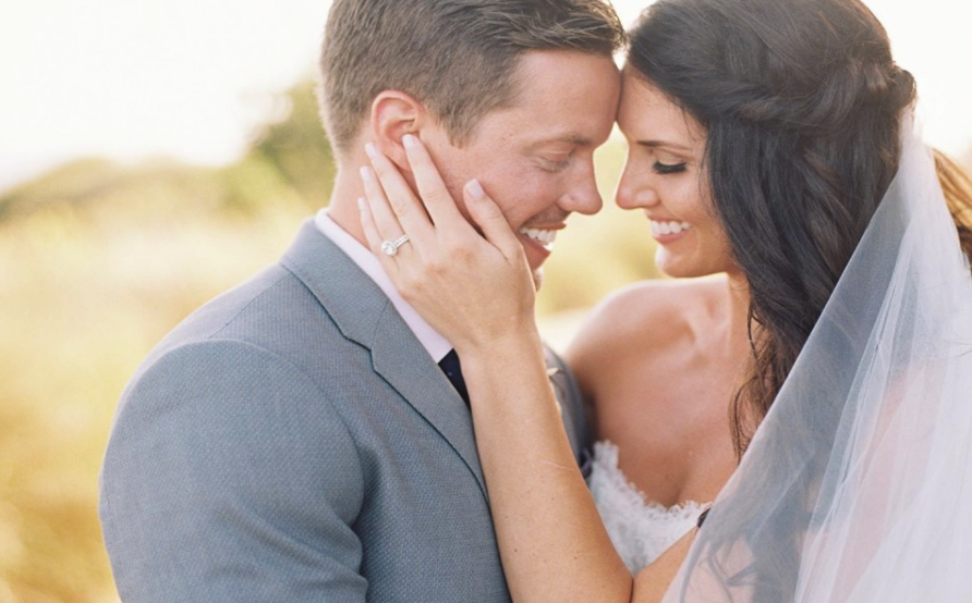 Brunette Bride with Twisted Hairstyle, Veil and simple makeup in Wedding Photos with Husband outside. Bridal hair and makeup by Vanity Belle in Orange County (Costa Mesa) and San Diego (La Jolla)