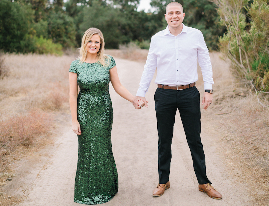 Outdoor Engagement Photos with Green Sequin Dress Holding Hands. Hair and Makeup done by Vanity Belle in Orange County (Costa Mesa) and San Diego (La Jolla).
