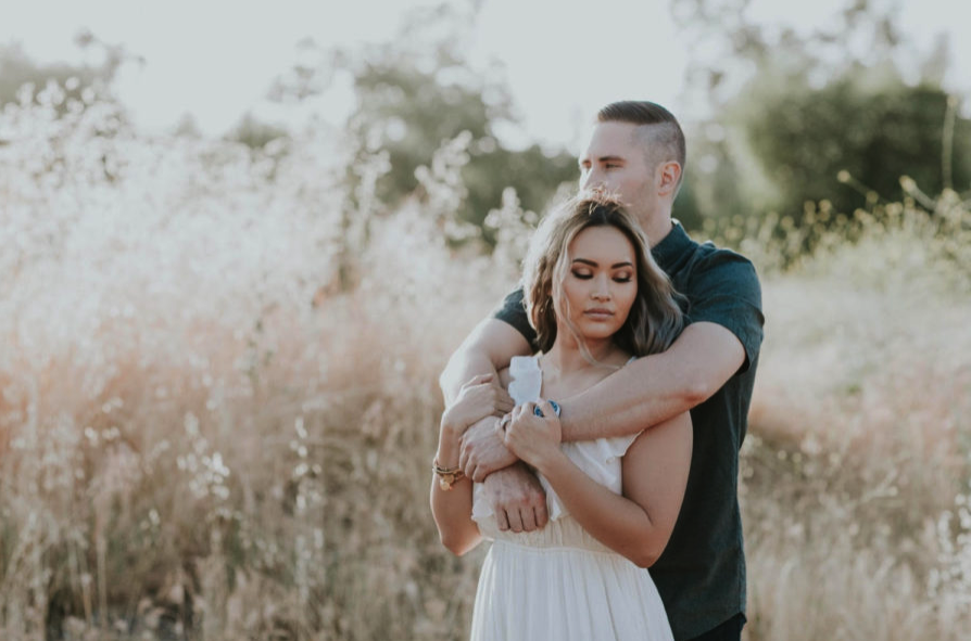 Engagement Photos in Nature with Couple Hugging. Hair and Makeup done by Vanity Belle in Orange County (Costa Mesa) and San Diego (La Jolla).