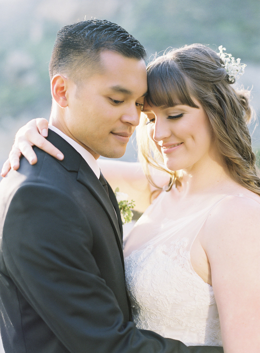 Brunette Bride with Bangs and Hair Down Hugging Husband outdoors. Wedding Hair and Makeup by Vanity Belle in Orange County (Costa Mesa) and San Diego (La Jolla)