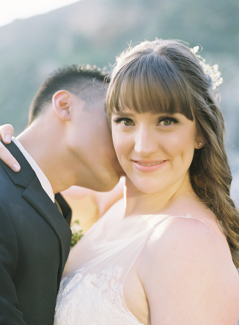 Brunette Bride with Bangs and Hair Down with Husband Kissing Neck. Wedding Hair and Makeup by Vanity Belle in Orange County (Costa Mesa) and San Diego (La Jolla)