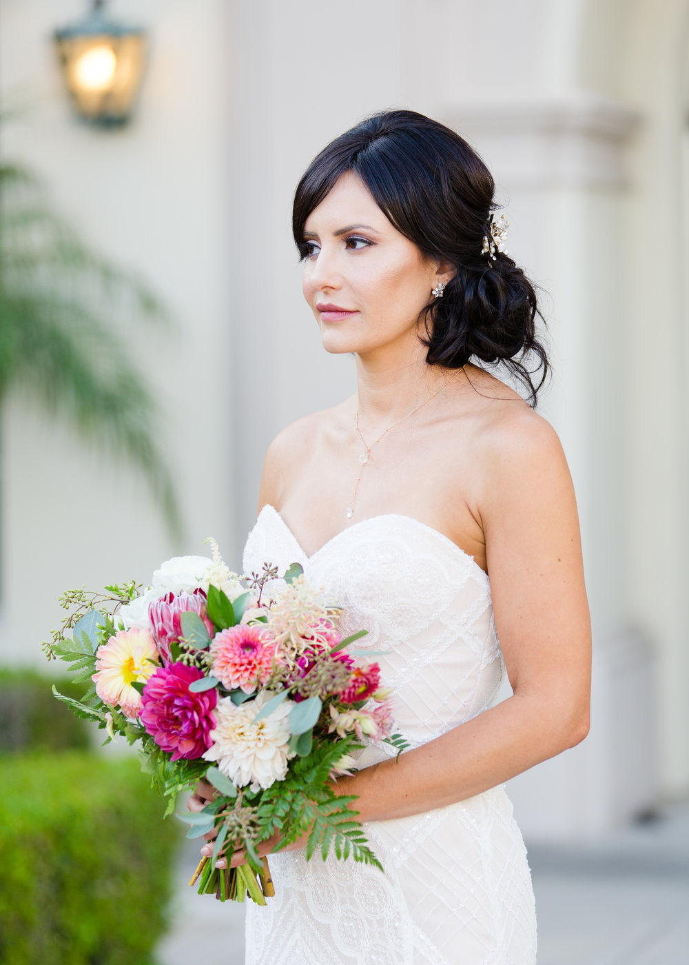 Brunette Bride with Updo Hairstyle holding bouquet outside in Wedding Photography. Bridal Hair and Makeup by Vanity Belle in Orange County (Costa Mesa) and San Diego (La Jolla)