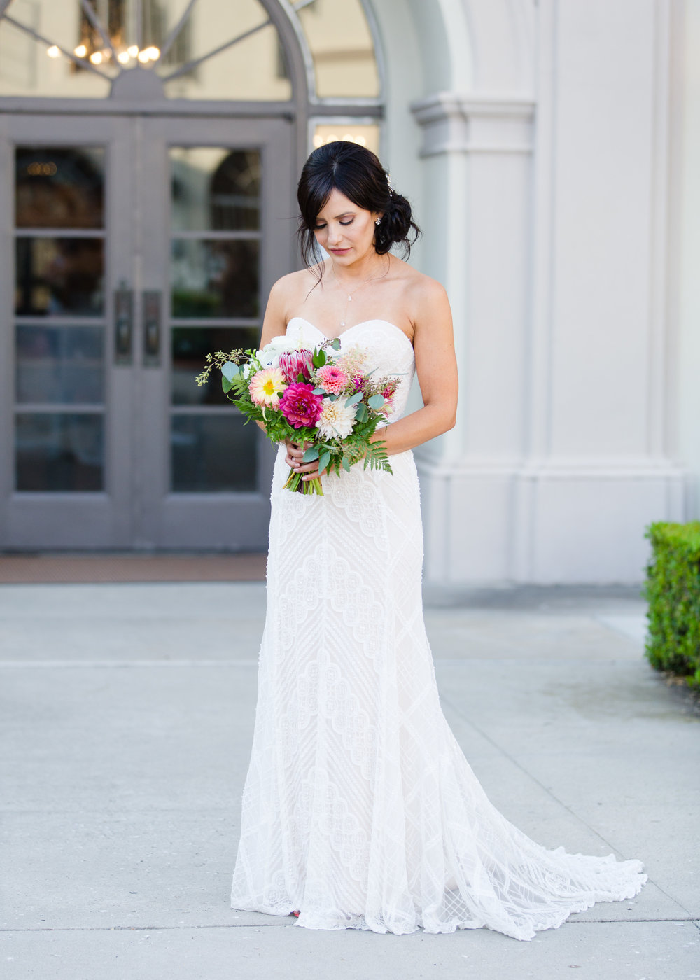 We are absolutely in LOVE with her lace and jeweled gown from The White Dress. This style gives a truly elegant and vintage look that is complimented perfectly with her bouquet of swoon worthy blooms by floral designer Rebecca Eichten.