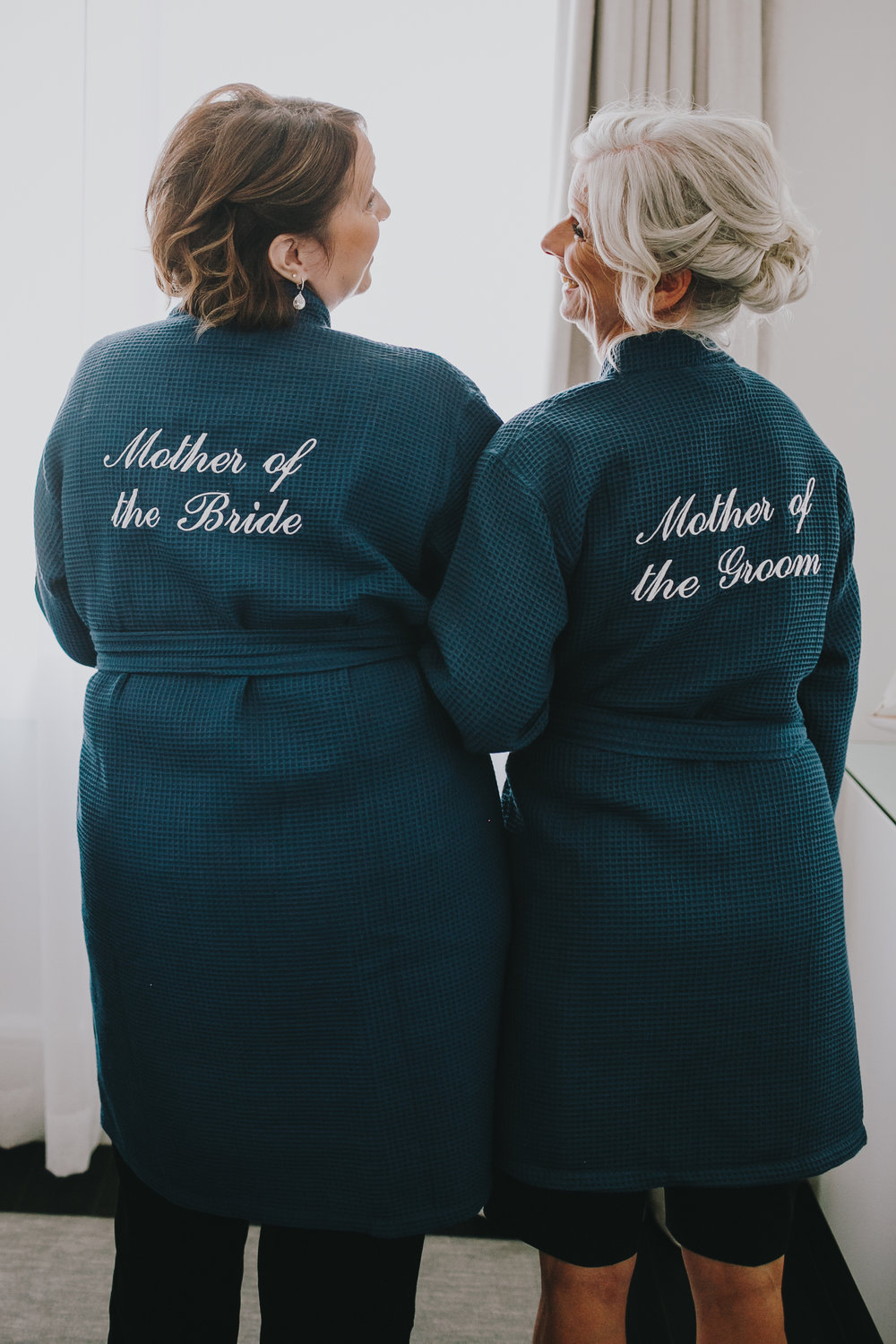 "Such a special moment captured between the wedding ""moms."" What a special way to use matching robes!"
