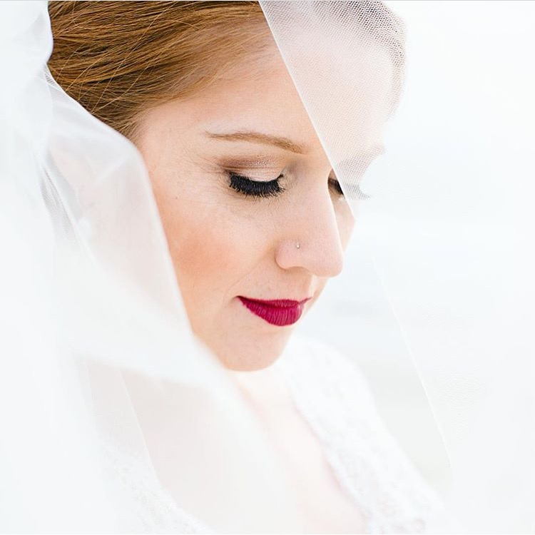 Looking for a style that truly POPs!? Then, go for a gorgeous lip color to contrast all that white. Nothing looks more stunning than a Bride with bright lips complimented by peachy blush cheeks under a weding veil. Photo Credit: katherinebethphotography
