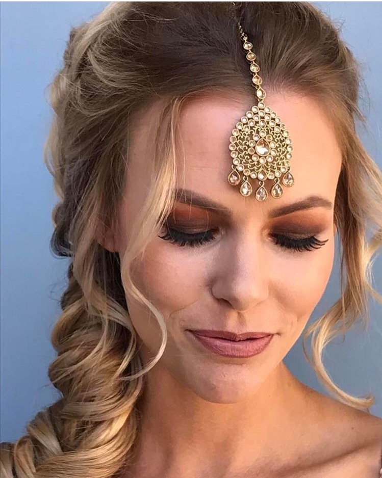 Brides are going Bronzy. Our artists are using more natural,monochromatic toned makeup in many Bridal looks. The deep rich tones above really compliment the Brides soft features. We loves how she ties in the entire look with a unique gold statement hairpiece.