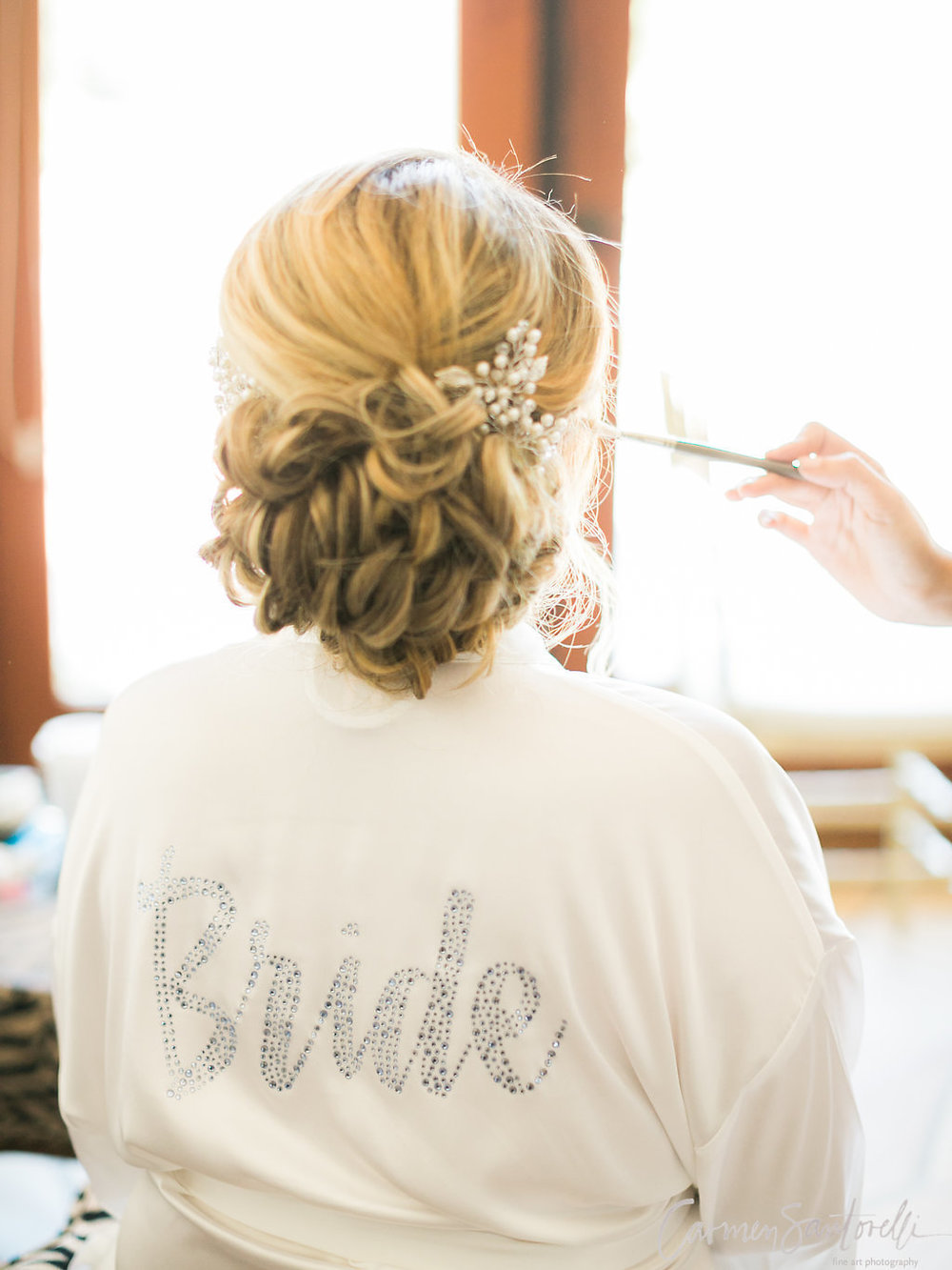 We are in love with this low, and a little to the side, textured bun. The textured twists give the up-do a more elaborate style, while accentuating the Brides balayage.Adding in a chic hairpiece gives the stle an extra dreamy, natural look.