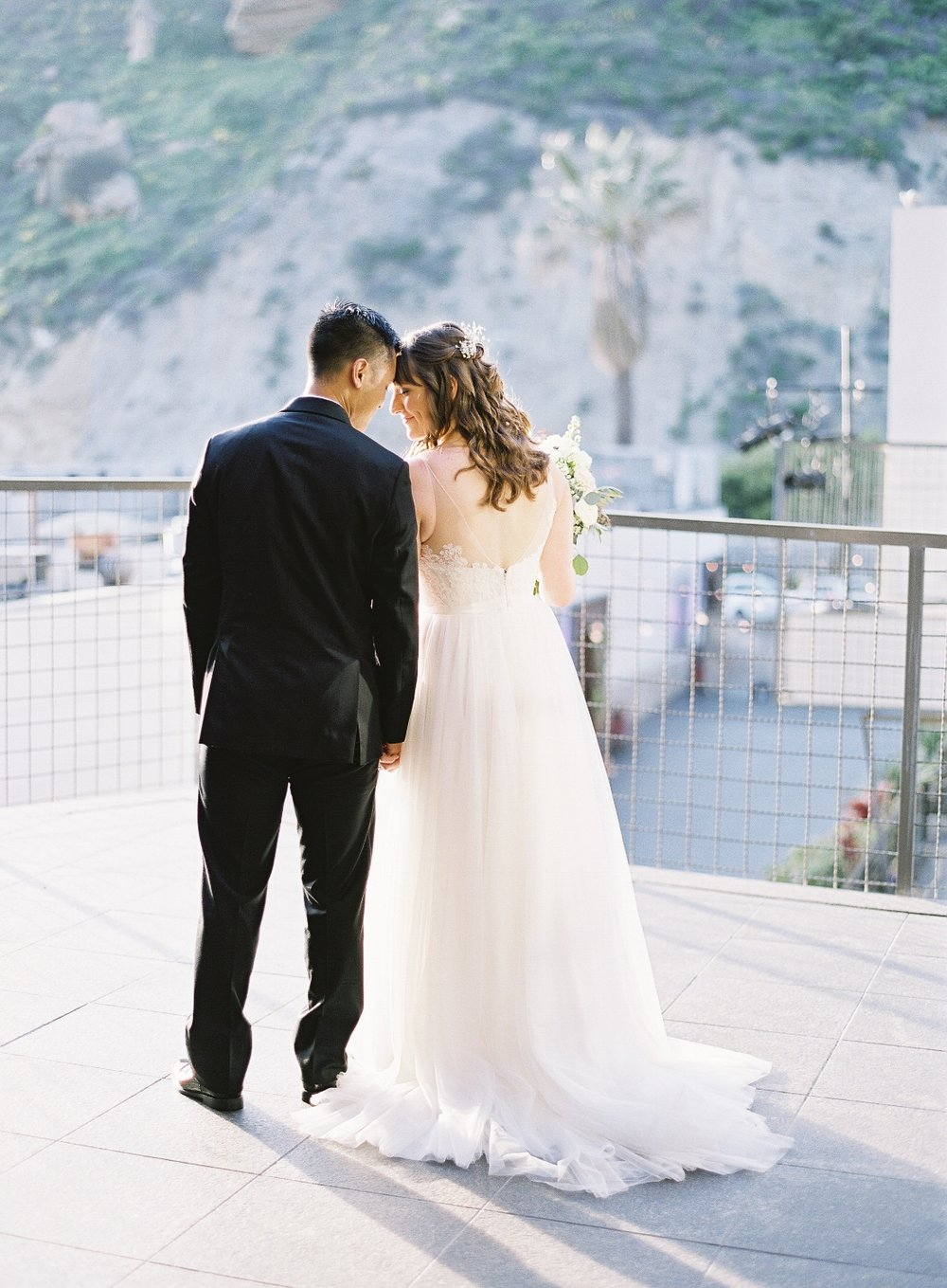 Wedding Photo with Couple from Behind. Bridal Hairstyles and makeup by Vanity Belle in Orange County (Costa Mesa) and San Diego (La Jolla)