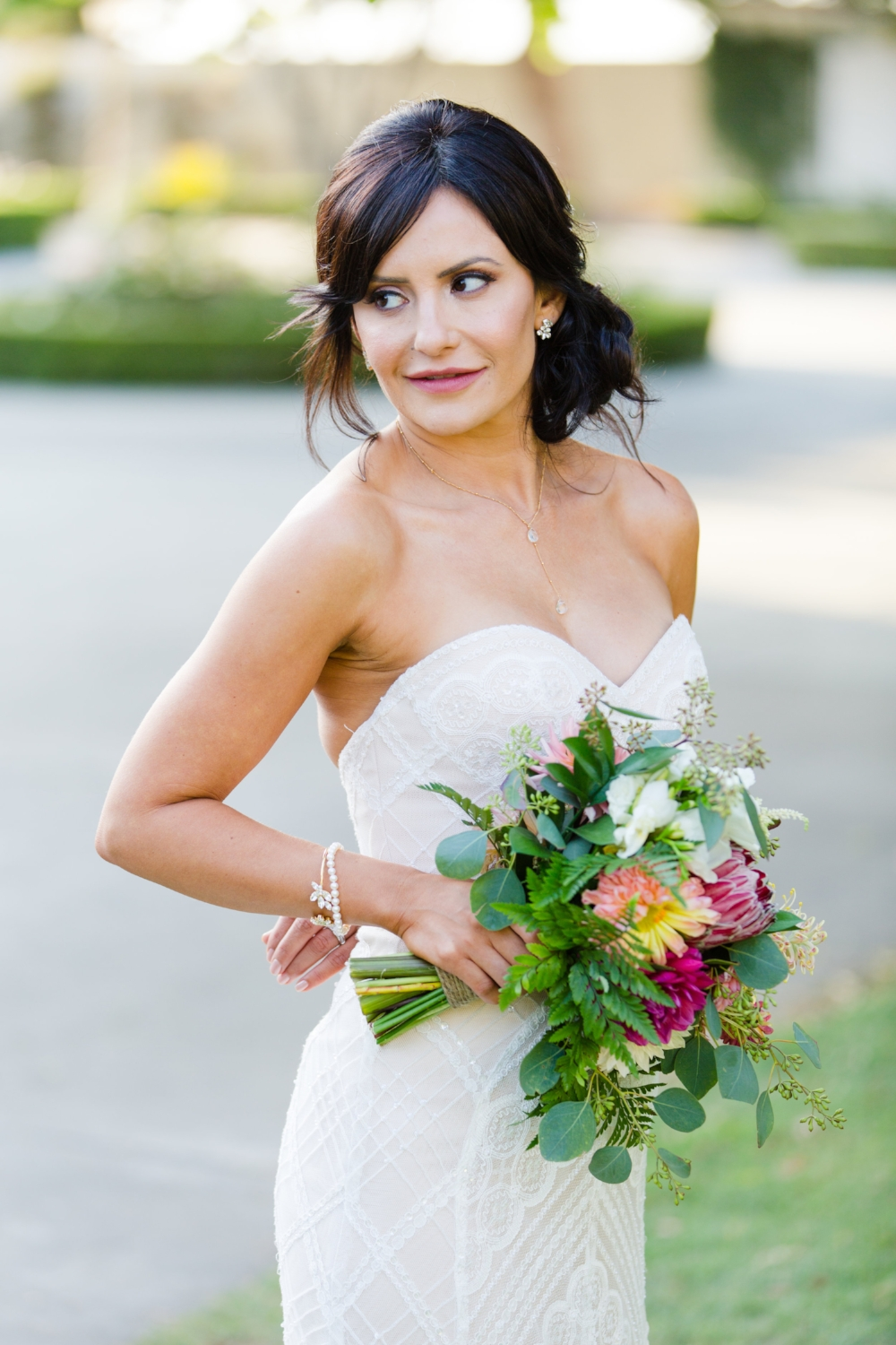 Brunette Bride with Updo holding bouquet outside in Wedding Photography. Bridal Hair and Makeup by Vanity Belle in Orange County (Costa Mesa) and San Diego (La Jolla)