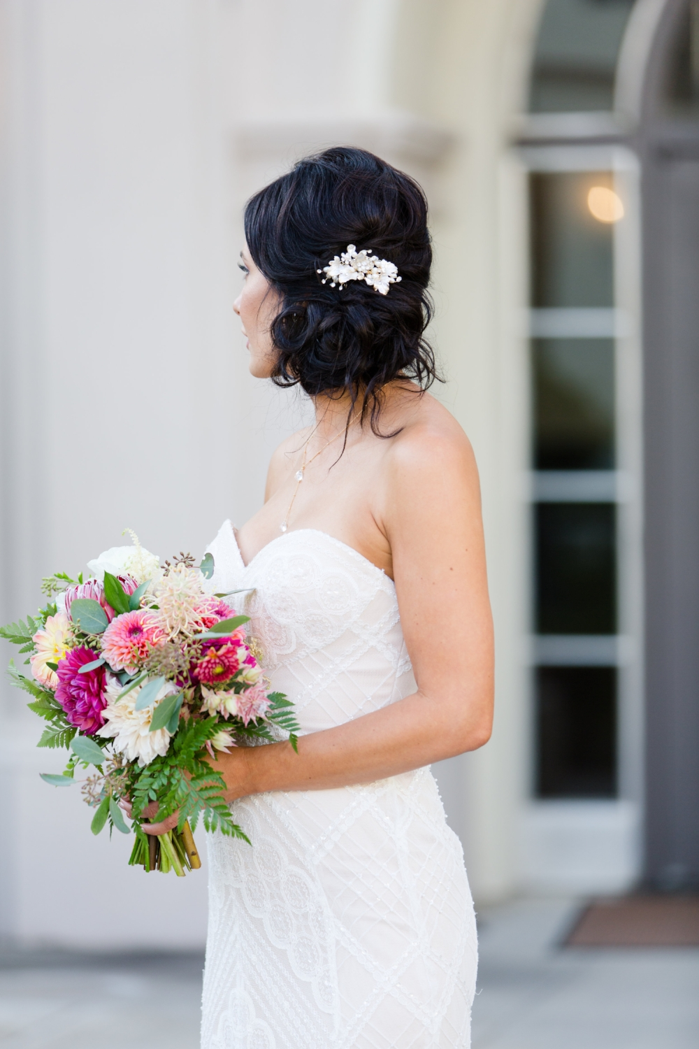 Brunette Bride with Updo and hair accessory holding bouquet outside in Wedding Photography. Bridal Hairstyles and Makeup by Vanity Belle in Orange County (Costa Mesa) and San Diego (La Jolla)