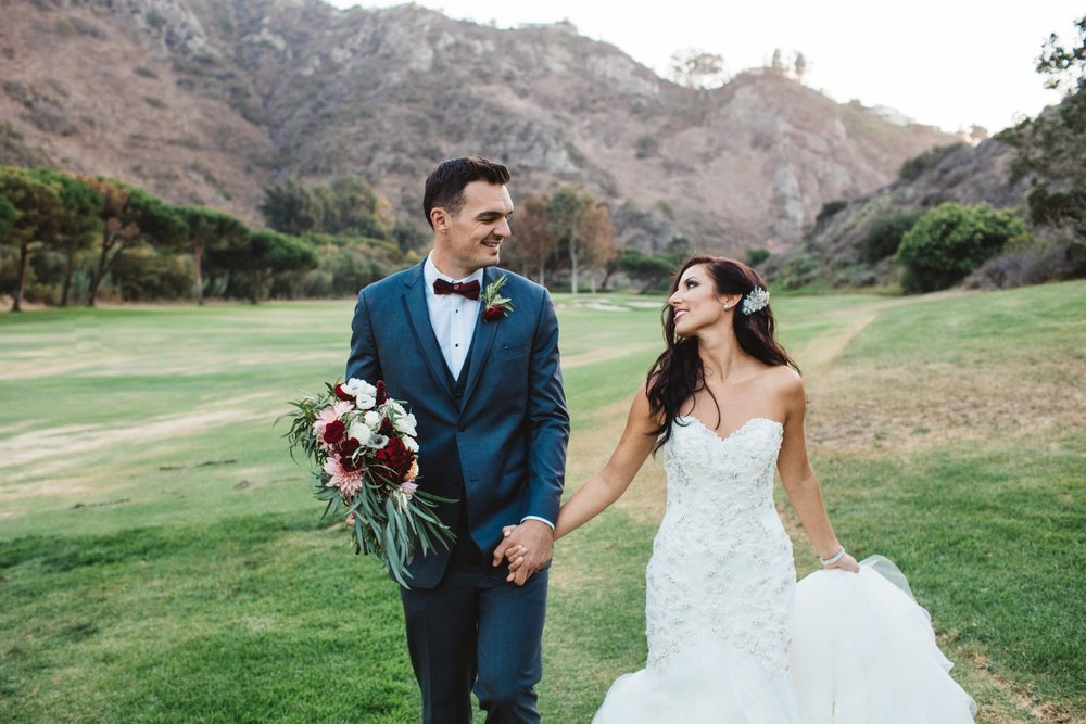 Brunette Bride with Long Hairstyle Down holding hands with Husband in Outdoor Wedding Photos. Bridal hair and makeup by Vanity Belle in Orange County (Costa Mesa) and San Diego (La Jolla)