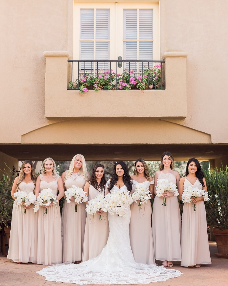Wedding day outdoor photography with champagne bridesmaid dresses and orchid bouquets at Surf & Sand in Laguna Beach, CA. Bridal hair and makeup by Vanity Belle in Orange County (Costa Mesa) and San Diego (La Jolla).