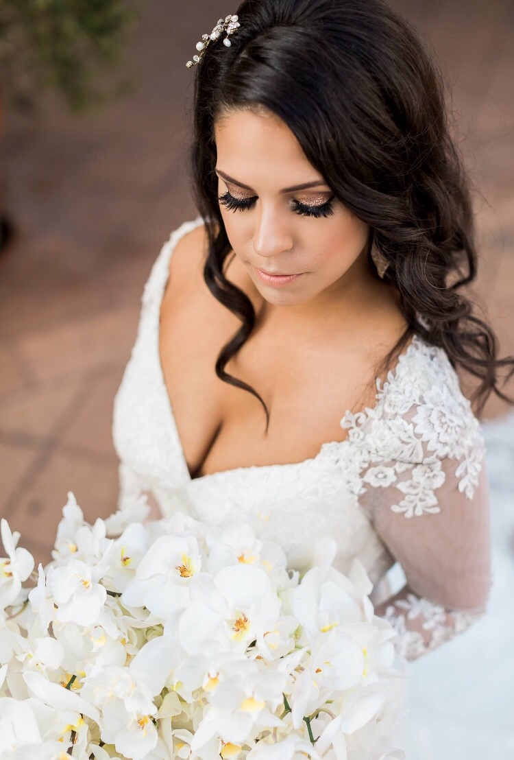 Hispanic brunette bridal makeup with sparkly smokey eye and curled hair down with veil and orchid bouquet. Wedding day Hair and Makeup by Vanity Belle in Orange County (Costa Mesa) and San Diego (La Jolla)