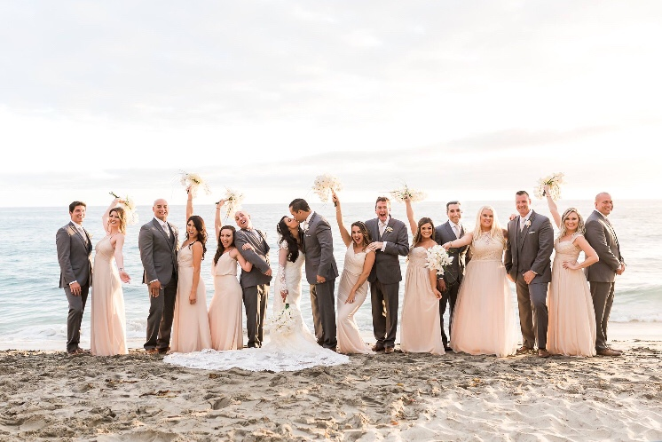 Beach Wedding day outdoor photography with bridal party in champagne bridesmaid dresses and orchid bouquets at Surf & Sand in Laguna Beach, CA. Bridal hair and makeup by Vanity Belle in Orange County (Costa Mesa) and San Diego (La Jolla).