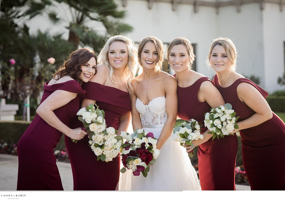Wedding day photography with bridal party in bold red dresses. Side up-do and wavy curls hair styles. Bride and bridesmaid beauty by Vanity Belle in Orange County (Costa Mesa) and San Diego). thevanitybelle.com