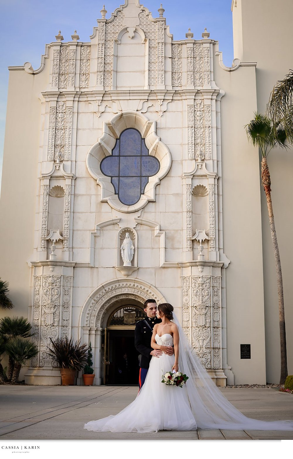 Brunette bride with groom outside the Immaculata Catholic Church in San Diego.  Bridal Beauty by Vanity Belle in Orange County (Costa Mesa) and San Diego (La Jolla). thevanitybelle.com