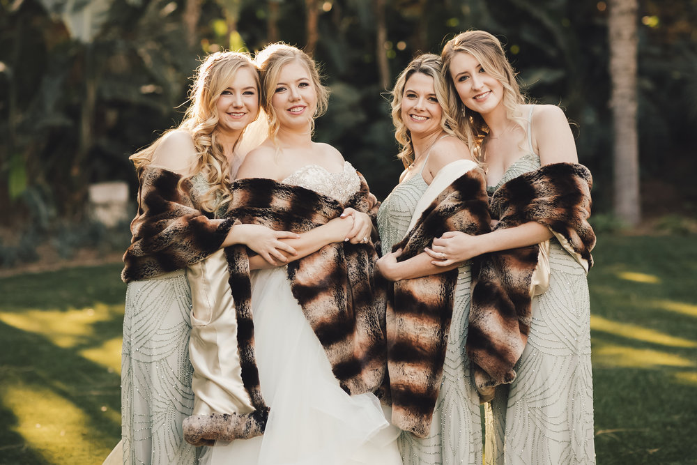 Bride and Bridesmaids taking fun photos in their fur shawls after Disney wedding ceremony. Bridal and bridesmaid hair and makeup by Vanity Belle in Orange County (Costa Mesa) and San Diego (La Jolla) thevanitybelle.com
