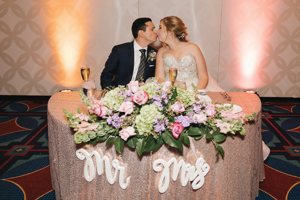 Bride and groom smooch at sweetheart table during Disney wedding reception.  Photographer by Analisa Joy Photography. Wedding hair and makeup beauty by Vanity Belle. www.thevanitybelle.com