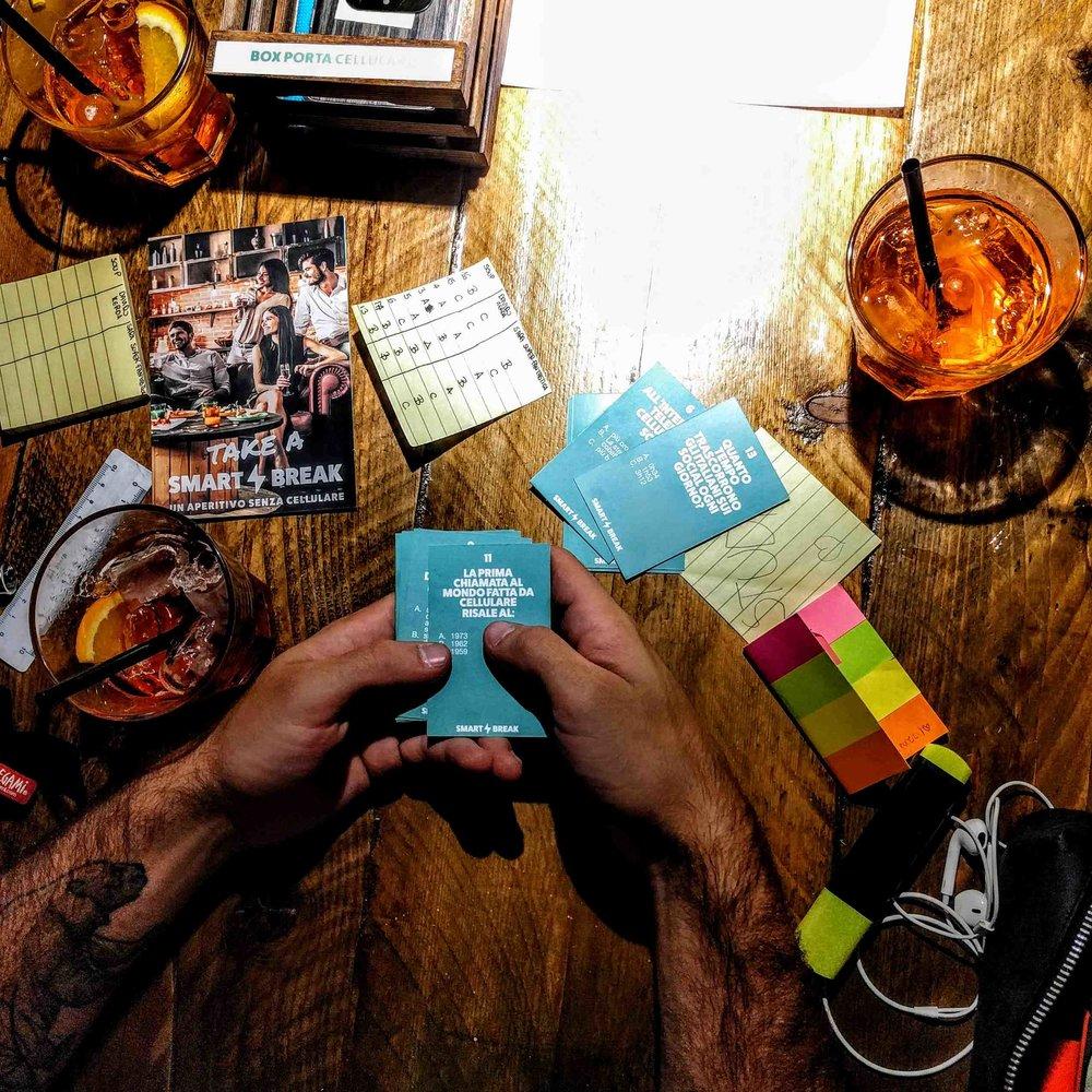 """Materiale plus - Cestini porta cellulare per ogni tavolo e quiz cartaceo """"Quanto ne sai di smartphone?"""" da lasciare ai clienti."""